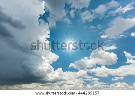 Blue sky with dark storm clouds and sun reflection - stock photo