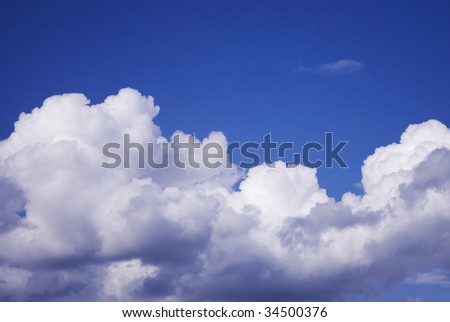 blue sky with fluffy cumulus clouds on bottom, copy space above - stock photo