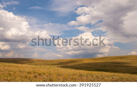 Blue sky with puffy clouds over grassland landscape - stock photo