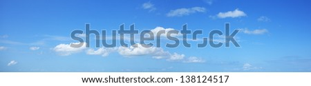 Blue sky with some white clouds. Panoramic shot. - stock photo