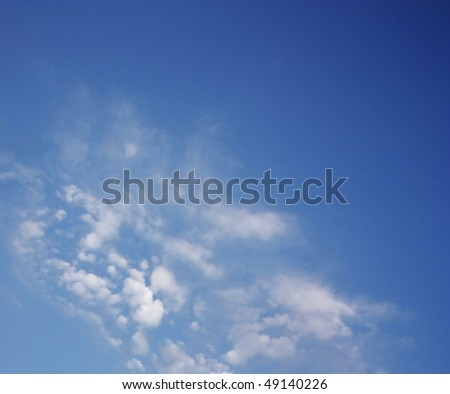 Blue sky with some white puffy clouds. - stock photo