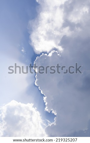 Blue sky with sunbeams and clouds.  - stock photo