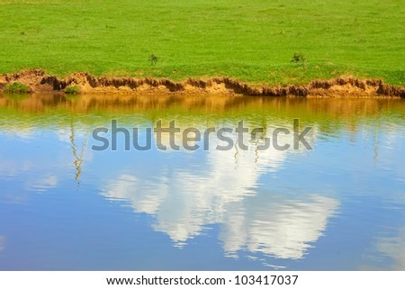Blue sky with white clouds reflected on a ponds water surface in springtime - stock photo
