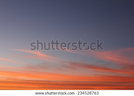 Blue sky with wispy orange clouds halfway across and orange layers of dense clouds below/Blue Clear Sky with Orange Cirrus halfway and Orange Strata of Dense Cumulus below/Blue and orange cloudscape - stock photo