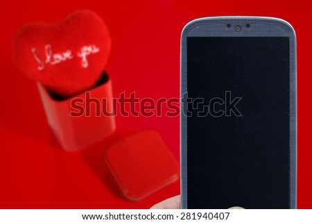 Blue smatrphone and I love you heart on red background. Idea for Valentines Day celebration, love, Father's or Mother's day, love apps, Internet, blogs and others. - stock photo