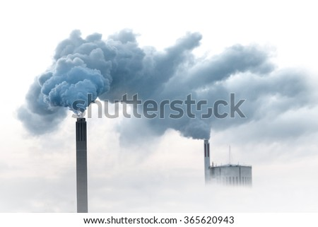 Blue smoke from chimneys of power plant - stock photo
