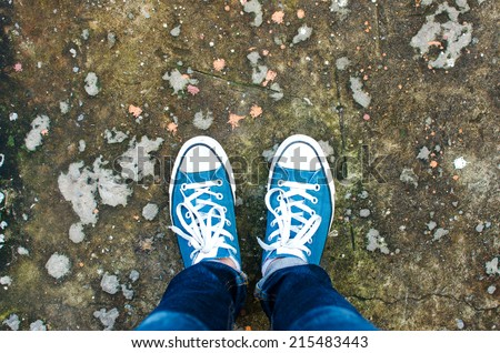 Blue Sneakers shoes walking on Dirty concrete top view , Canvas shoes walking on concrete - stock photo