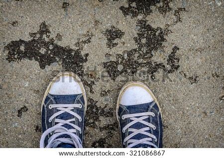 Blue sneakers shoes walking on old grange dirty concrete top view.  - stock photo