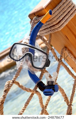 Blue Snorkeling equipment hanging on a rope, swimming pool on the background. - stock photo
