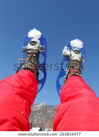 Blue Snowshoes and Red Ski suit in the mountains in winter - stock photo