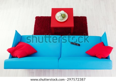 Blue sofa with red pillows and red coffee table, top view - stock photo