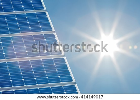 Blue solar panel with a bright sun shining on the right side - stock photo