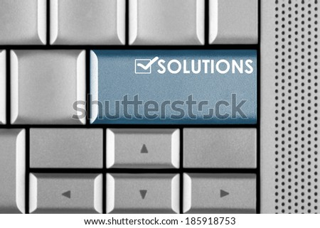 Blue SOLUTIONS key on a computer keyboard with clipping path around the SOLUTIONS key - stock photo