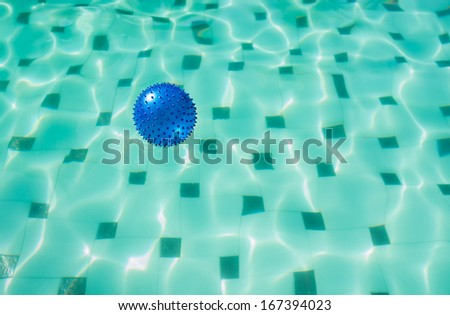Blue spike ball floating in a swimming pool - stock photo