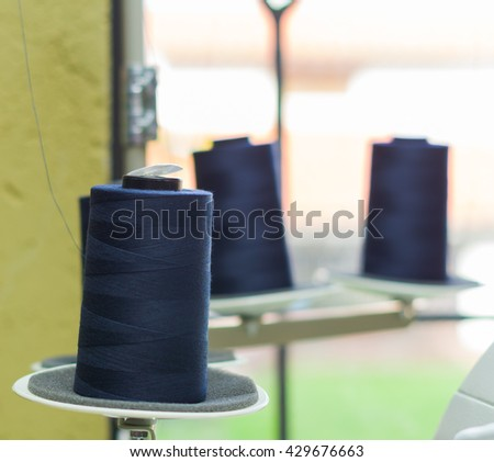 Blue spool of thread ready to be used in a sewing machine, behind other spools - stock photo