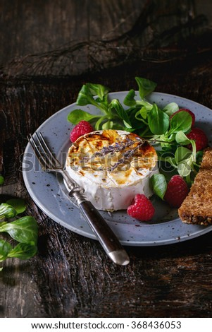 Blue spotted plate with grilled goat cheese served with liquid honey, lavender, raspberries, wholegrain toast and green salad. With vintage fork over old wooden table. Dark rustic style. - stock photo