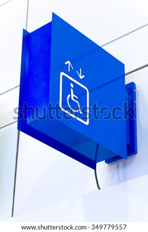 Blue square handicap sign with wheelchair elevator isolated on white background. (Selective Focus) - stock photo