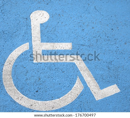 Blue square handicap sign with wheelchair painted on street - stock photo