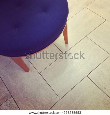 Blue stool on tile floor. Modern furniture. - stock photo