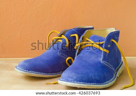 Blue suede shoes A shoestring yellow A suede classic style luxury Casual accommodation on the wooden floor - stock photo