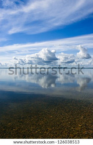 Blue summer sky with white clouds reflecting in lake - stock photo