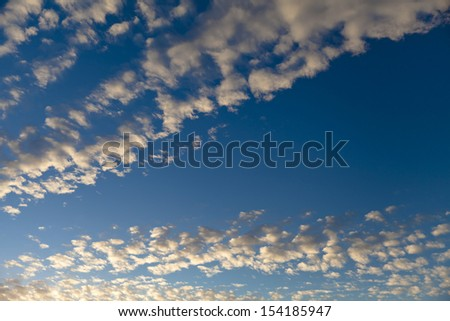 Blue sunny sky with small puffy clouds - stock photo