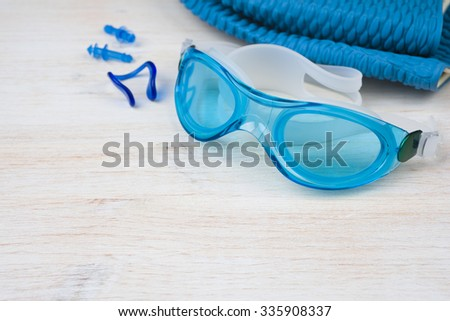 Blue swimming equipment on wooden background. Sport concept - stock photo