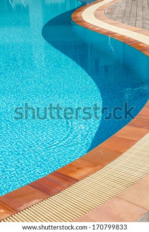 Blue swimming pool and brown stone margin - stock photo