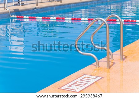 blue swimming pool at hotel with stair. - stock photo