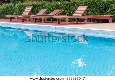 blue swimming pool in green garden of the resort - stock photo
