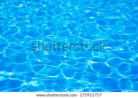 Blue swimming pool rippled water with sunny reflections background - stock photo