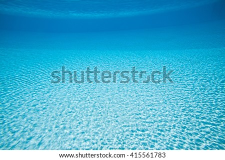Blue swimming pool rippled water with sunny reflections underwater background - stock photo