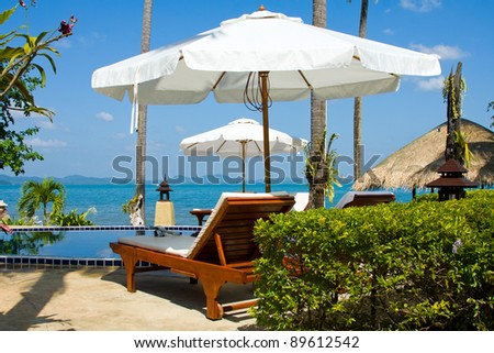 Blue swimming pool water and palm trees near the sea. Summer vacations in tropical resort. - stock photo