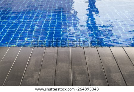 blue swimming pool with wood floor texture - stock photo