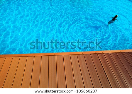 blue swimming pool with wood flooring stripes summer vacation - stock photo