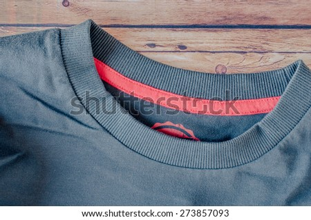 Blue T-Shirt close up on wooden background - stock photo