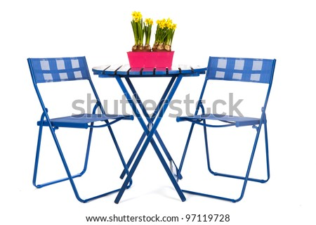 Blue table and chairs with spring daffodills - stock photo