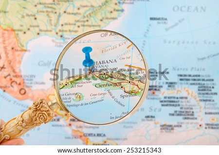 Blue tack on map of Caribbean with magnifying glass looking in on Havana or Habana, Cuba - stock photo