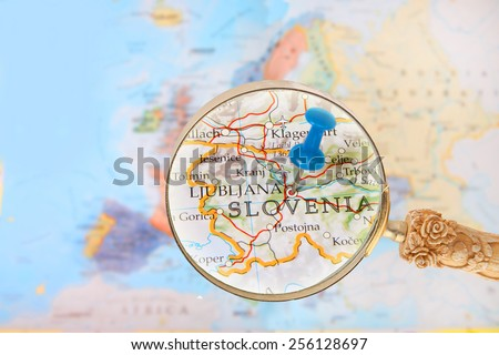 Blue tack on map of Europe with magnifying glass looking in on Ljubljana, Slovenia - stock photo