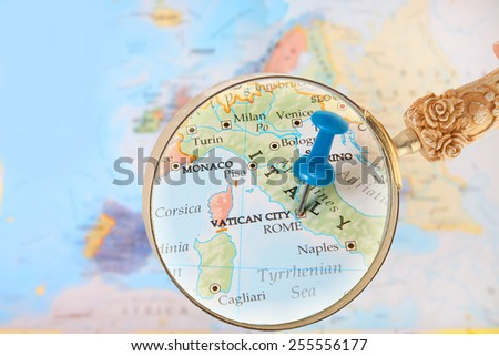 Blue tack on map of Europe with magnifying glass looking in on Rome, and Vatican City, Italy - stock photo