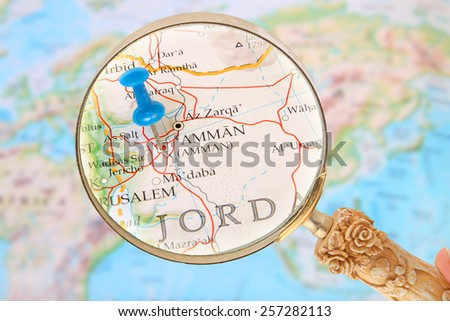 Blue tack on map of the world with magnifying glass looking in on Amman, Jordan, Asia - stock photo