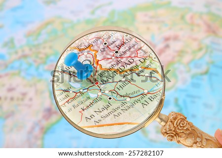 Blue tack on map of  the world with magnifying glass looking in on Baghdad, Iraq, Middle East in Asia - stock photo