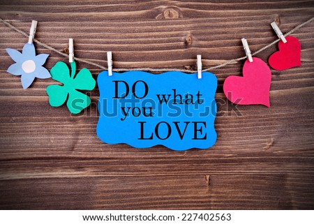 Blue Tag With Phrase Do What You Love On It Hanging on a Line with Different Symbols Like A Flower, Four-leaf Clover And A Heart On Wooden Background - stock photo