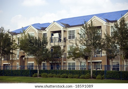 Blue tarps covering the damaged roofs of an apartment complex in the aftermath of a hurricane. - stock photo