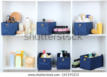 Blue textile boxes with cosmetic products for personal care in white shelves  - stock photo