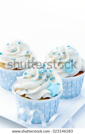 Blue theme cupcakes with white butter cream frosting and baby blue decorations - stock photo