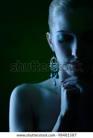 Blue tinted portrait of beautiful young blonde woman with hands below her chin - stock photo