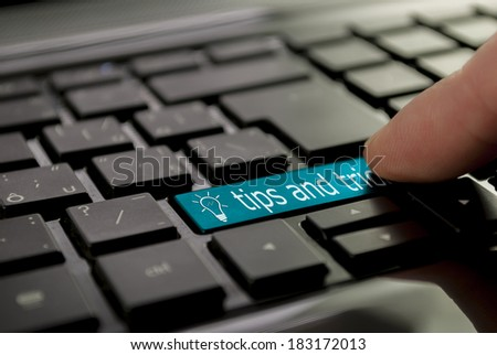 blue tips and tricks button or key on black keyboard - stock photo