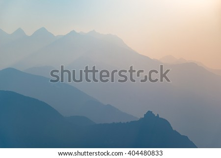 Blue toned distant mountain range of the Alps with St. Michel Abbey profile at the bottom. Torino Province, Piedmont, Italy. Telephoto view, soft light at sunset. - stock photo