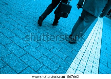 Blue toned photo of two business men walking, highly saturated - stock photo